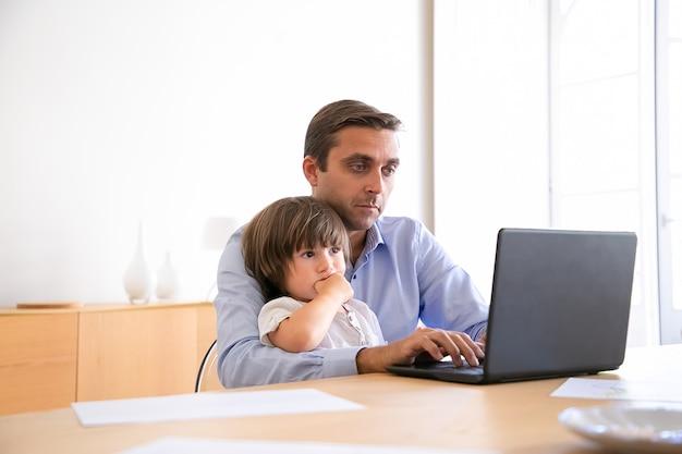 Серьезный отец просматривает интернет на ноутбуке и держит милый сын. кавказский мужчина средних лет в рубашке, сидя за столом с ребенком, глядя на экран и работая. отцовство и домашняя концепция