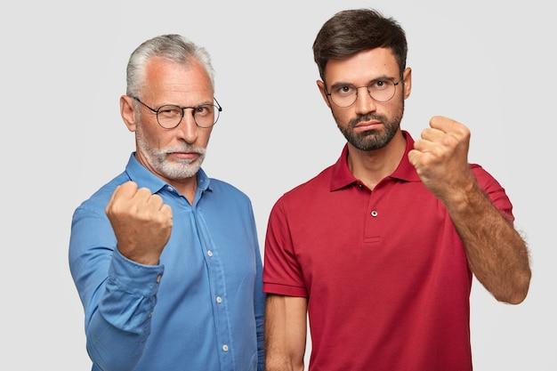 Padre serio e giovane figlio adulto in posa contro il muro bianco