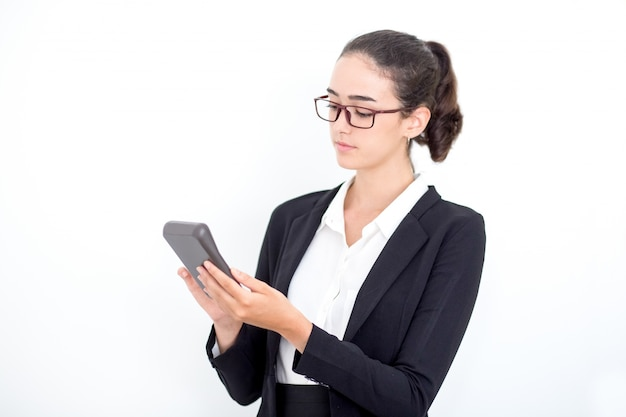 Serious female accountant counting on calculator