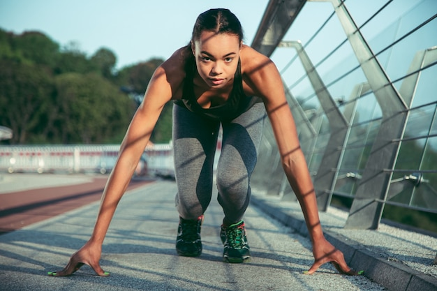 다리에서 달리기 전에 땅에 손을 대고 있는 진지한 여성 운동선수