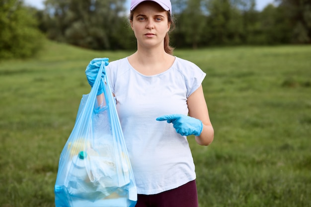 Serious female in baseball cap and t shirt, lady with garbage bag in one hand