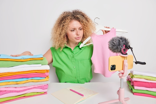 Serious female blogger involved in distance purchasing shares new brand clothes holds pink shirt on hanger records live stream video poses around neatly folded laundry sells outfit through e store