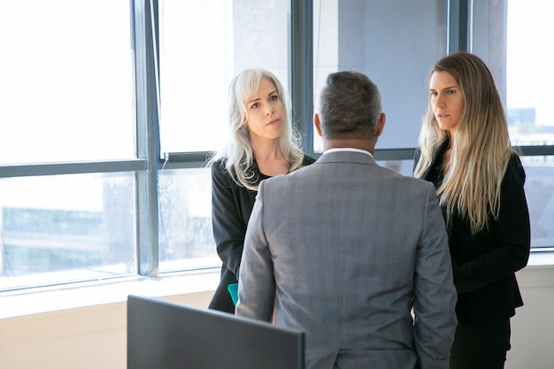 Serious female business colleagues talking to male boss together, standing in office, discussing project. medium shot, back view. business communication or group meeting concept