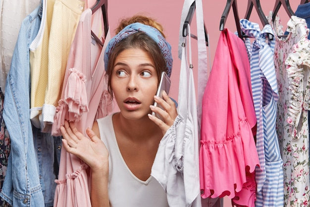Serious female chatting over mobile phone while looking through rack with clothes, taking advice in her best friend what to wear on date with her boyfriend, having special occasion. clothing concept