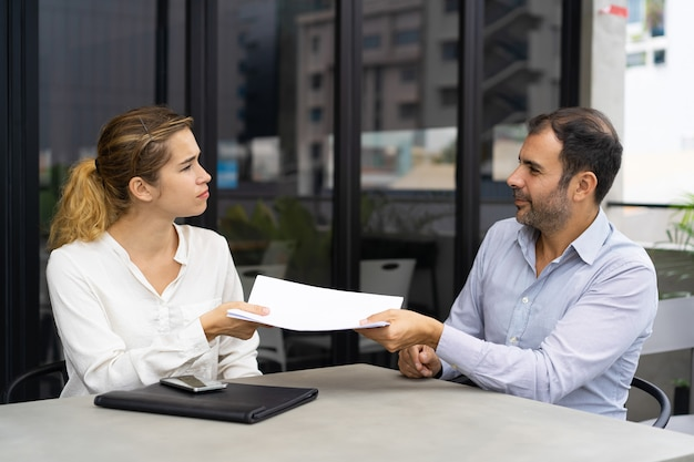 Serious female client giving document to financial consultant