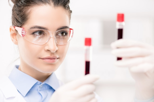 Serious female clinician in protective eyeglasses looking at samples of new vaccine developed in laboratory