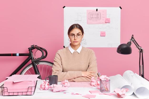 真面目な女性デザイナーがオフィスのデスクトップでポーズをとって、紙のスケッチに囲まれた建築プロジェクトを準備します