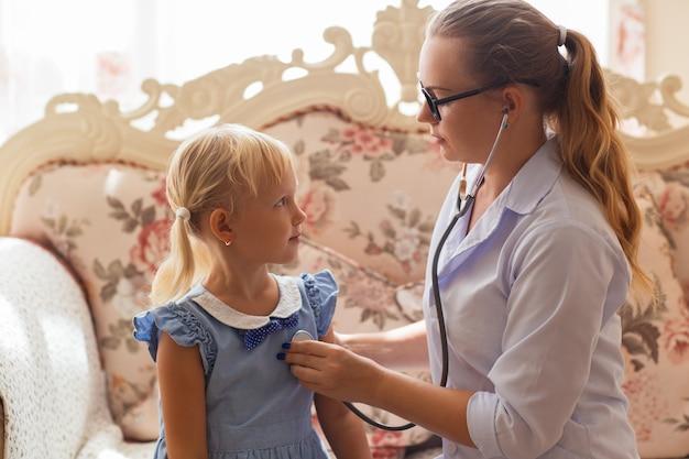 Серьезная женщина-врач осматривает маленькую девочку