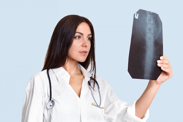 Serious female doctor looks attentively at x ray