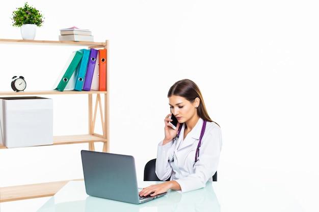 Серьезная женщина-врач сидит за партой во время разговора с кем-то по телефону и с помощью своего ноутбука