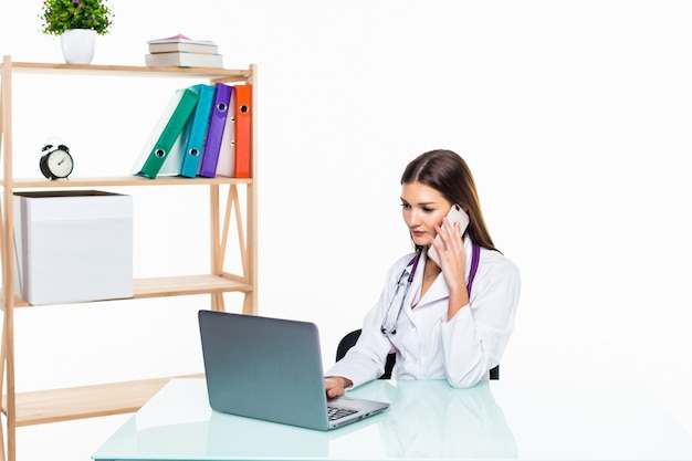 Serious female doctor sitting at her desk while calling to someone over the phone and using her laptop