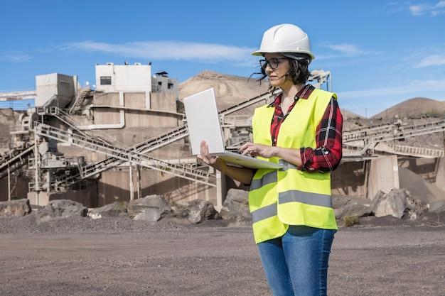 Серьезная женщина-инженер в каске и жилете ищет информацию на ноутбуке, стоя возле промышленного объекта строительной площадки