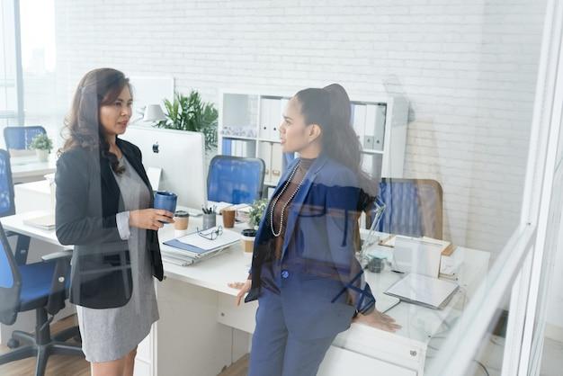 コーヒーブレイク中に会社の発展についてのニュースを議論する深刻な女性起業家