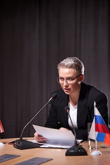 Serious female in eyeglasses with short hair sits at business conference using microphone while giving speech to partners. multi-ethnic executives gathered together. portrait of woman in formal suit
