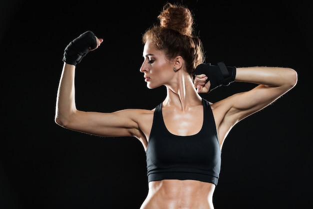 Serious female fighter showing her biceps