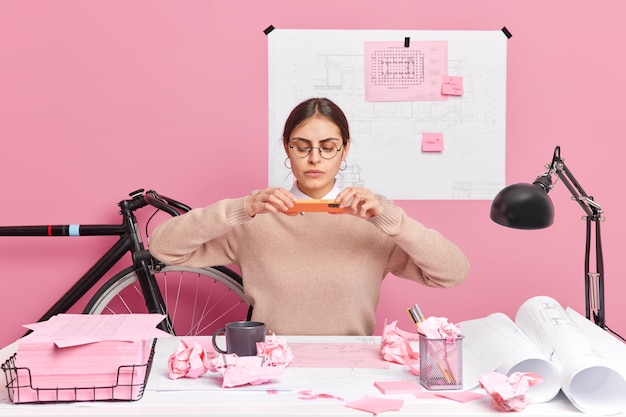 Serious female graphic designer makes photo of her sketch via smartphone poses at messy desktop with craft paper rolls makes blueprints of architectural construction wears round spectacles jumper.