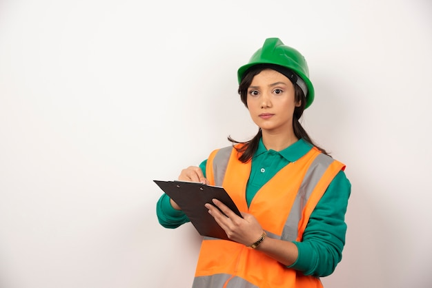 Serious female industrial engineer in uniform with clipboard on white background.