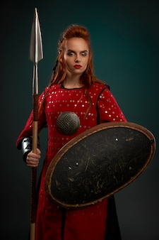 Serious female knight posing with shield and spear.