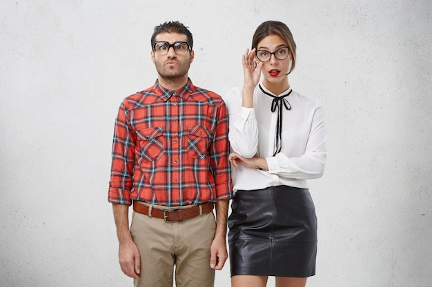 Le donne e gli uomini seri in occhiali e abiti formali hanno espressioni perplesse e rigorose