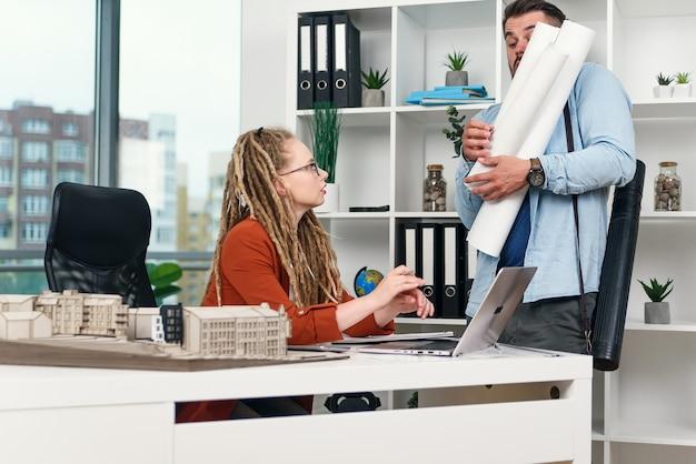 デザインエージェンシーの真面目な女性マネージャーは、不器用な労働者が彼女のテーブルに青写真を出したことに腹を立てている。