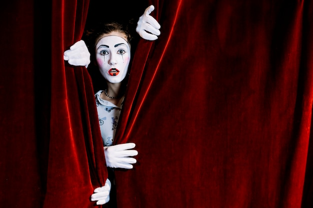 Serious female mime artist peeking from red curtain
