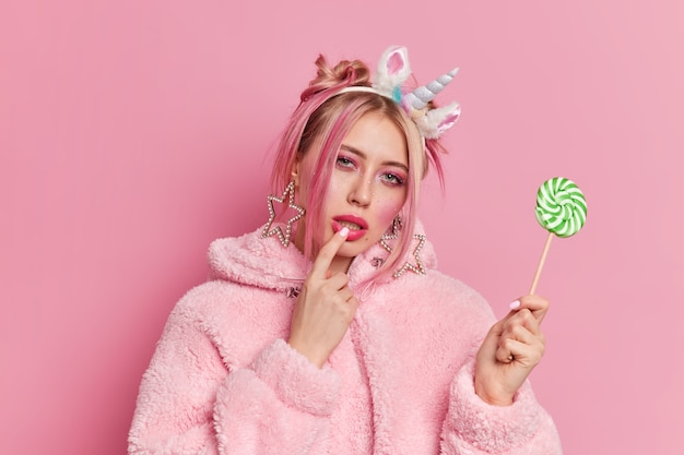 Serious female model with bright makeup keeps finger on lips looks mysteriously at camera holds green lollipop