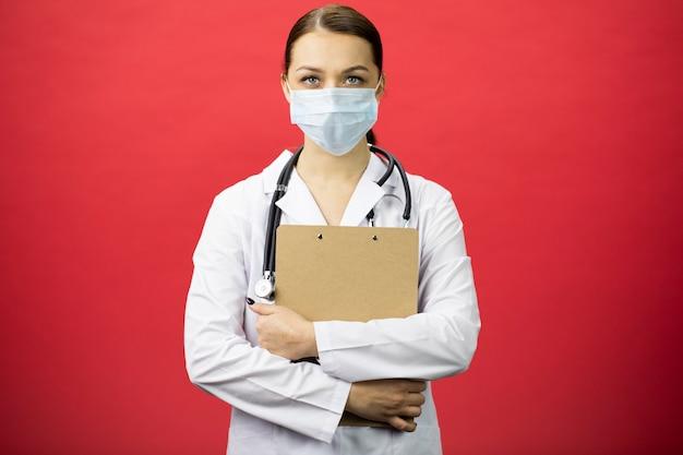 손에 클립 보드를 들고 보호 마스크에 심각한 여성 간호사