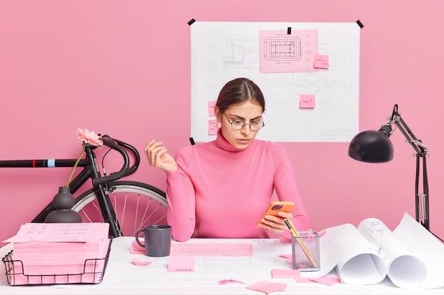 스마트 폰 디스플레이 creats 건축가 프로젝트에 집중된 심각한 여성 회사원은 종이 작업을하는 학습 과정에 관련된 코 워킹 공간에서 청사진 스케치 포즈를 사용합니다. 생산적인 작업
