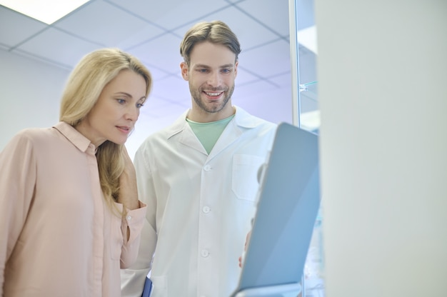 Serious female patient and a joyous male doctor scrutinizing something