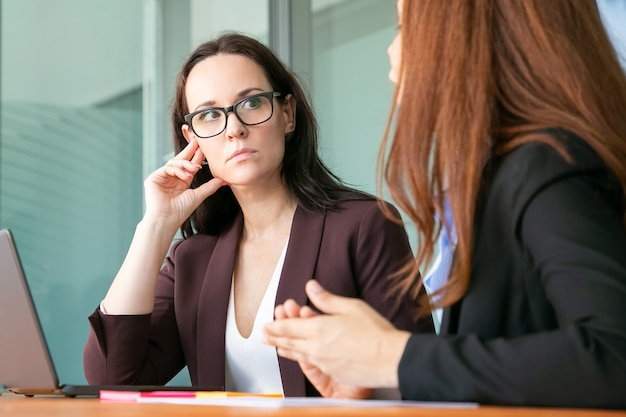 Serious female professional wearing glasses and office suit, listening to colleague at corporate meeting.