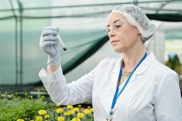 토양 샘플이 있는 플라스크를 보고 있는 진지한 여성 연구원