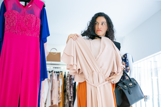 멀리 찾고 자신에게 드레스를 적용 천으로 옷걸이를 들고 심각한 여성 구매자. 전면보기. 패션 스토어 또는 소매 개념