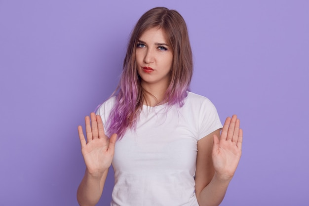 Serious female showing palms to camera, looking with strict expressing and ban gesture, forbids somebody to do bad things, isolated over purple wall.