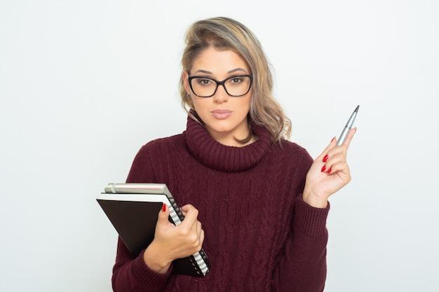 Серьезная студентка с книгами и ручкой