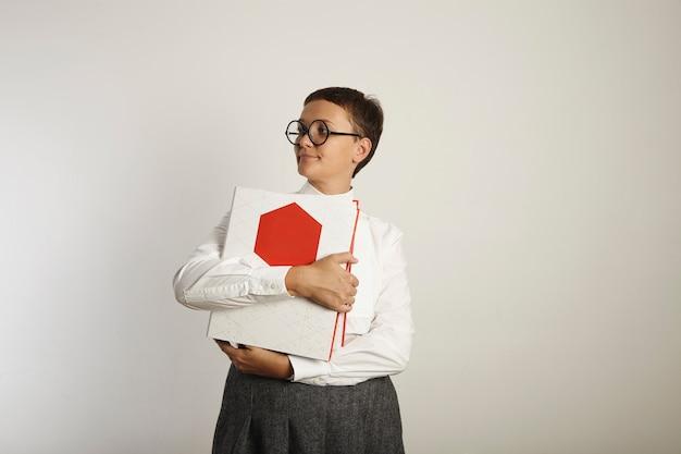 白い壁に背が高く立って目をそらし、明るい赤と白のバインダーを抱き締める退屈な服を着た真面目な女教師