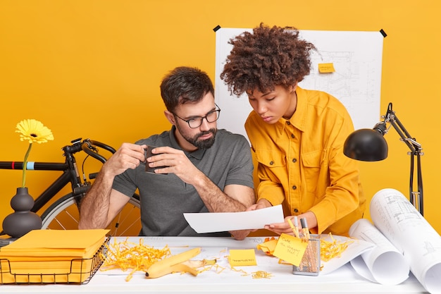 Serious female trainee shows paper to employer presents her ideas for future project pose at office desk with stickers blueprints yellow wall. diverse woman and man students collaborate