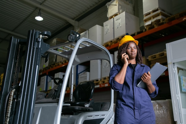 Serious female warehouse employee in hardhat standing near forklift and talking on mobile phone. shelves with goods in background. copy space. labor or communication concept