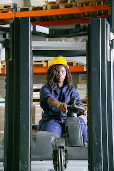 Serious female warehouse worker in hardhat driving fork lift, looking at front