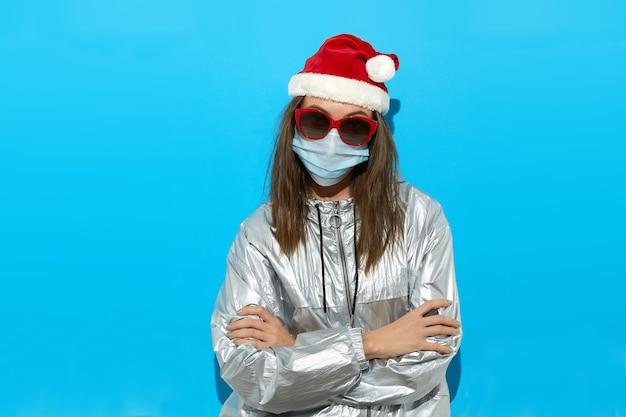 Серьезная женщина в шляпе санты, защитной маске и красных солнцезащитных очках