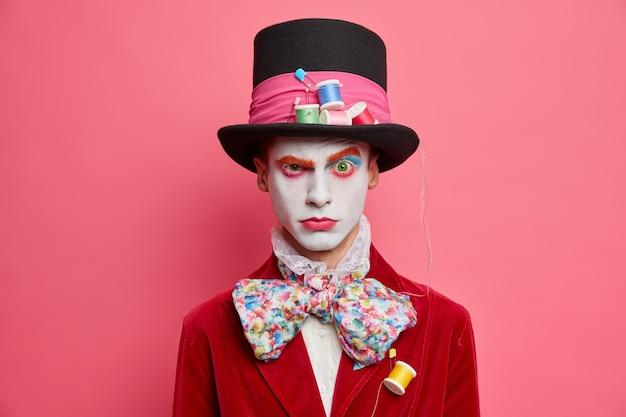 Il partecipante serio al festival ha un trucco luminoso, indossa lenti verdi sugli occhi alza le sopracciglia, indossa un cappello a cilindro e fa una cravatta a farfalla in posa contro il muro roseo