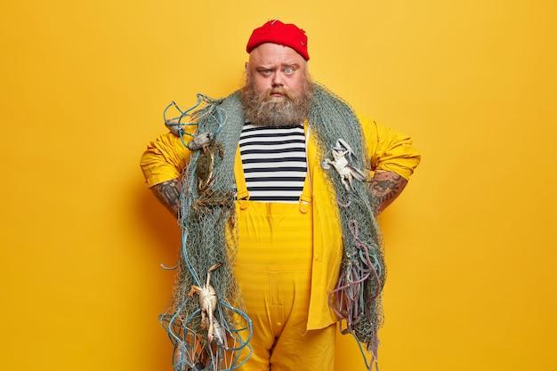 Il pescatore serio guarda con un'espressione sicura, tiene le mani sui fianchi, indossa una camicia da marinaio a righe e una tuta gialla, pronto a pescare con la rete