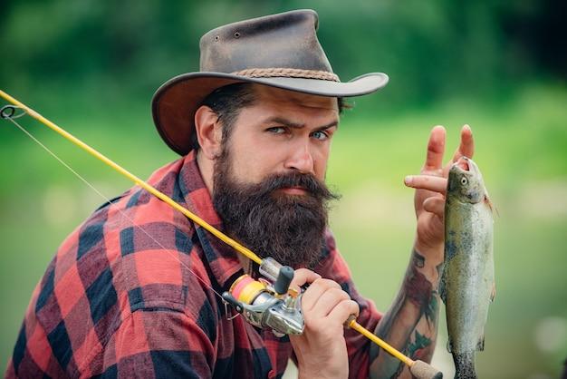물고기와 물 근처 심각한 어 부입니다. 낚싯대를 든 어부. 어부의 낚시 장비. 낚시는 재미있습니다. 자연에서 휴식을 취하십시오. 남자의 플라이피쉬 취미. 수염 난 남자. 프리미엄 사진
