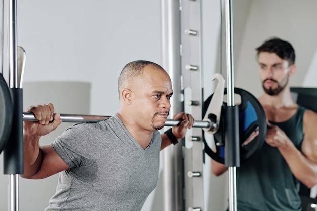 Серьезный тренер по фитнесу контролирует своего зрелого клиента, выполняющего приседания со штангой