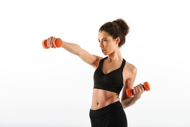 Serious fitness woman doing exercise with dumbbells and looking away