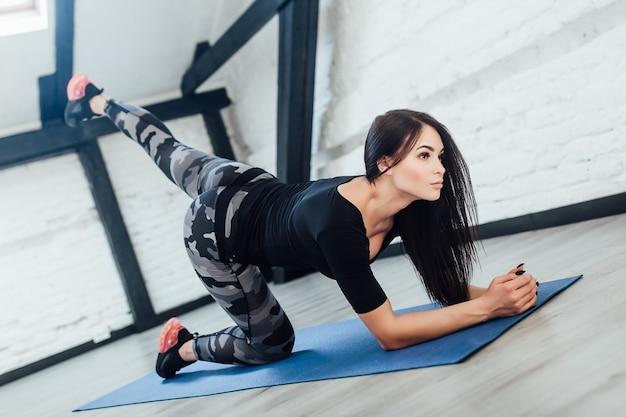 Серьезная женщина фитнеса протянулась перед тренировкой. она очень мила