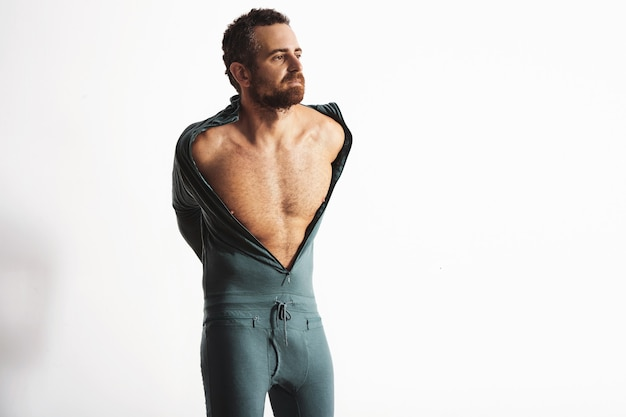 Atleta maschio serio e in forma con la barba che si veste con la sua calda tuta termica invernale da snowboard in lana merino