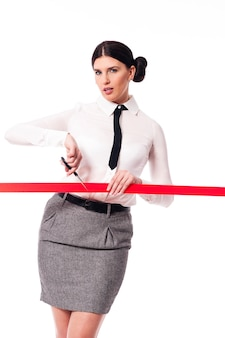 Serious and focus businesswoman cutting a red ribbon
