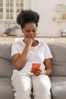 Serious focused black female read message on smartphone pensive girl get bad news in cell phone app