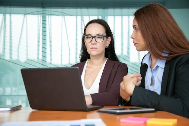 深刻な焦点を当てたビジネスの女性が会議のテーブルに座っている間、プロジェクトについて話し合い、ラップトップを使用しています。
