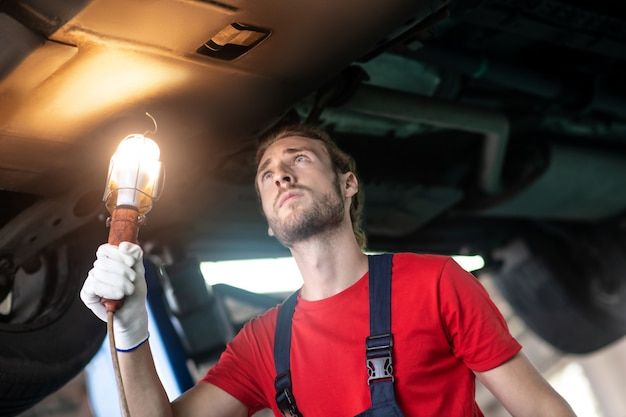 Serious focused car foreman in workwear standing with special lamp looking at underside of car